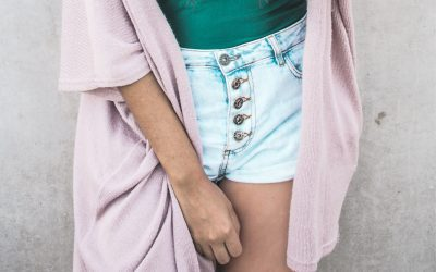 A woman's pelvic area covered by clothing but also covered by her hand.